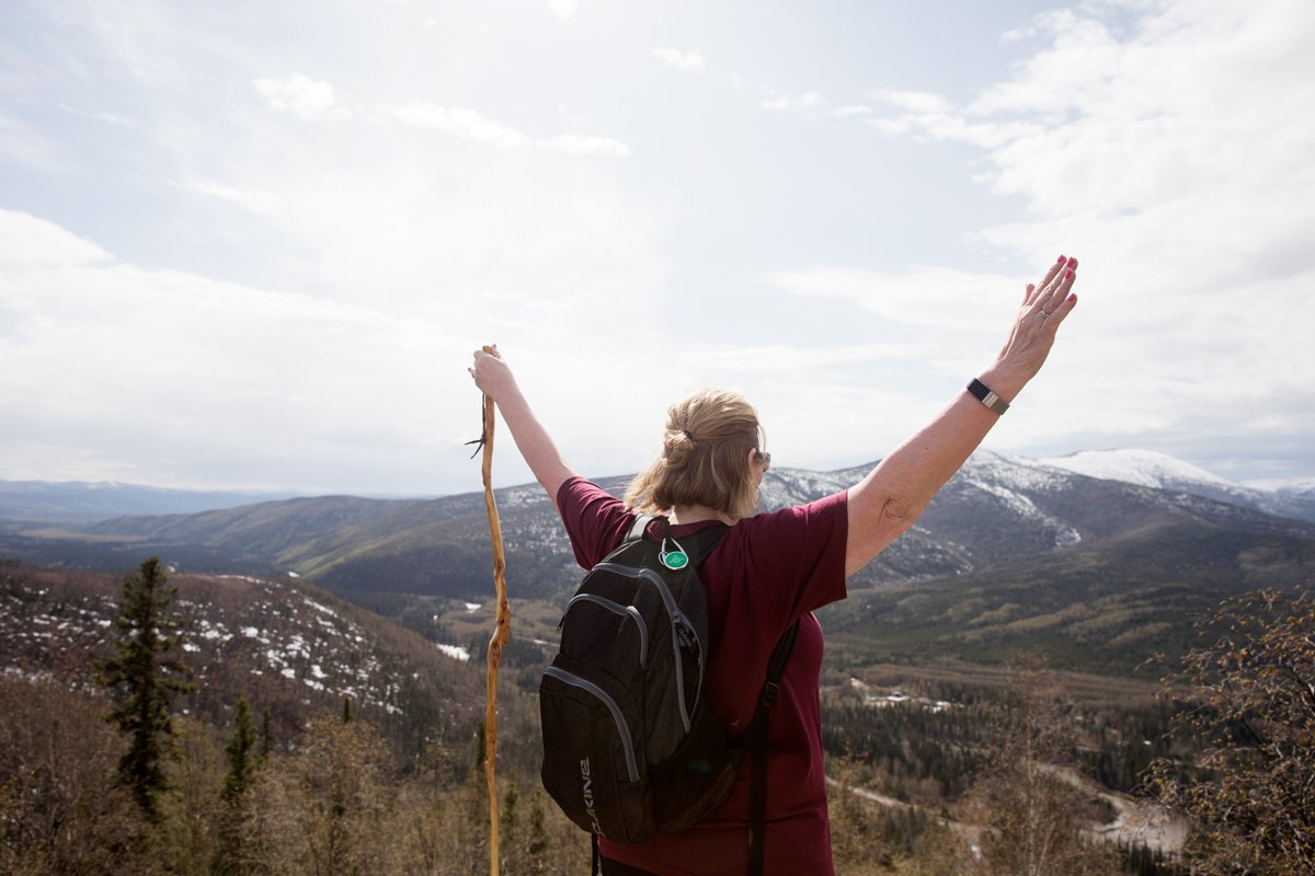 A woman waves her hands in the air as she overlooks a mountainous view in Alaska.